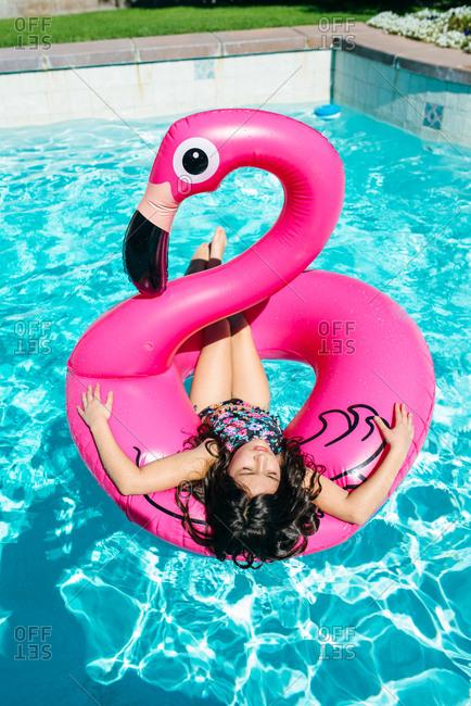 Girl lying on flamingo float in pool