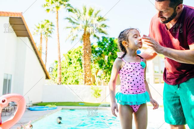 Man applies sunscreen to daughter's face