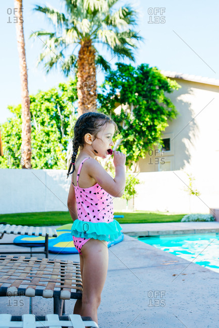 Young girl eating an ice pop by pool