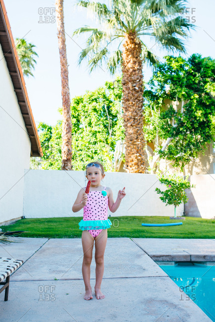 Young girl in swimsuit standing by pool with popsicle