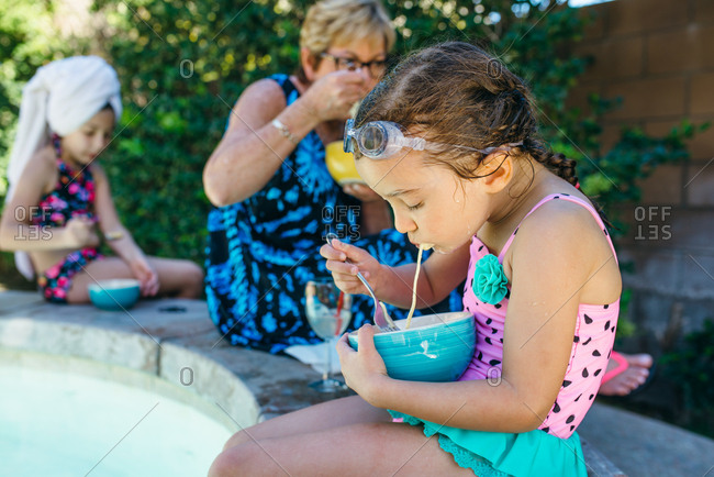 Girls eating pasta with grandmother outside by pool