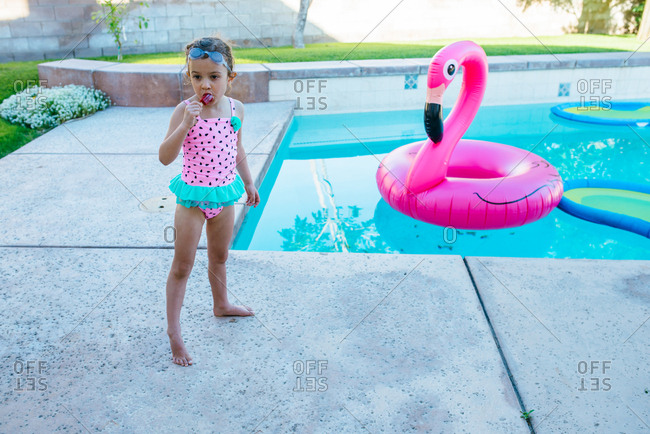 Girl eating popsicle by pool with flamingo float