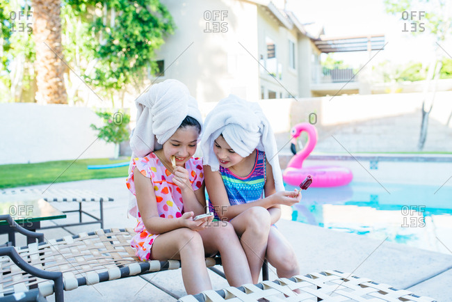 Two young girls with hair wrapped in towels look at smartphone