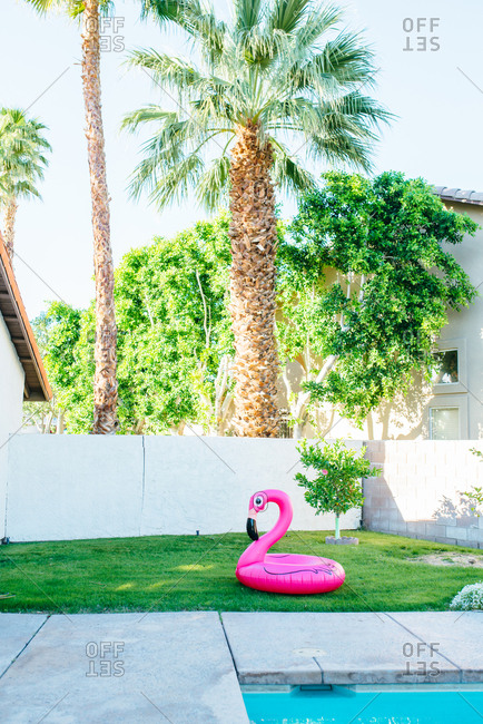 Pink flamingo float on grass next to pool