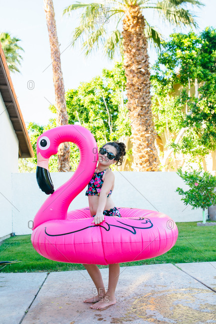 Young girl in swimsuit posing with flamingo float