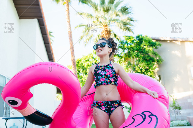 Girl playing with a pink flamingo float