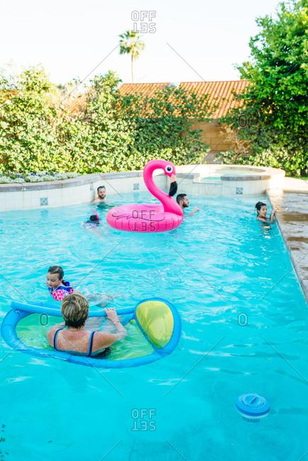 Family swimming in backyard pool