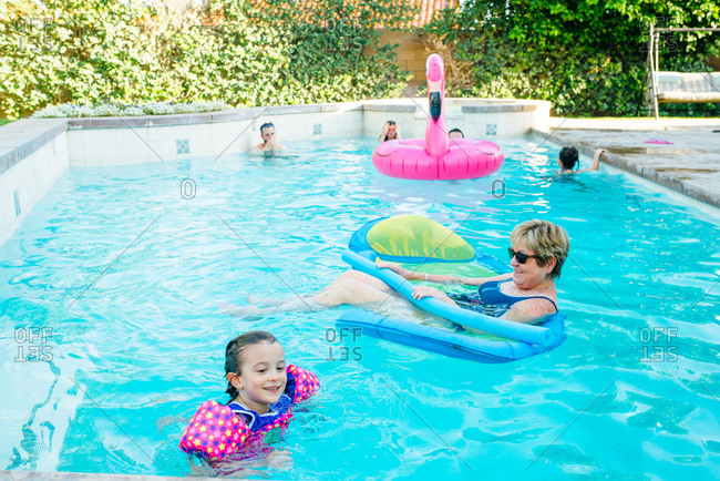 Grandmother and granddaughter playing in swimming pool
