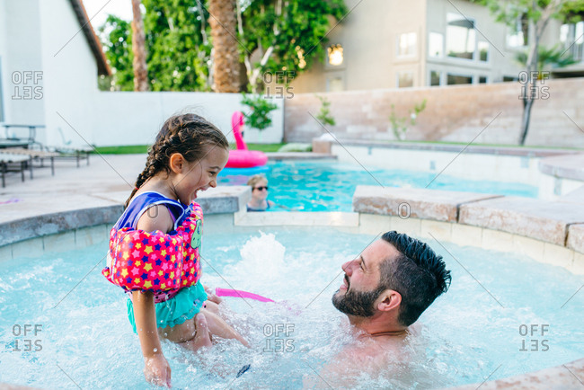 Man playing with daughter in outdoor spa