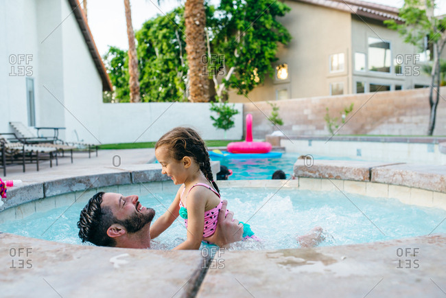 Father and daughter playing in hot tub