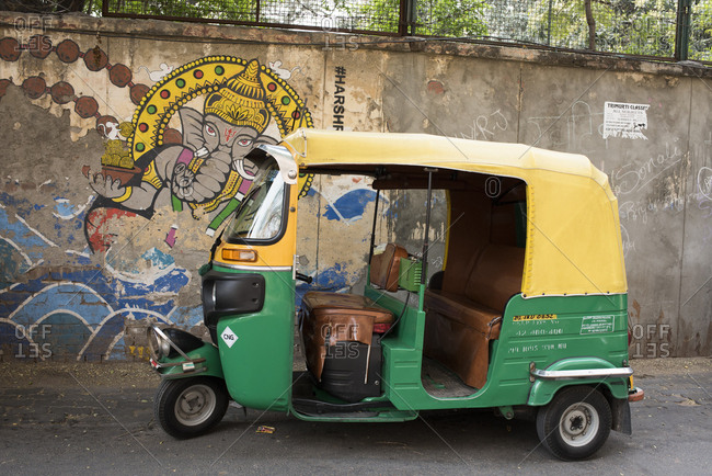 New Delhi, India - March 7, 2017: Rickshaw parked by street mural of Ganesh in New Delhi, India