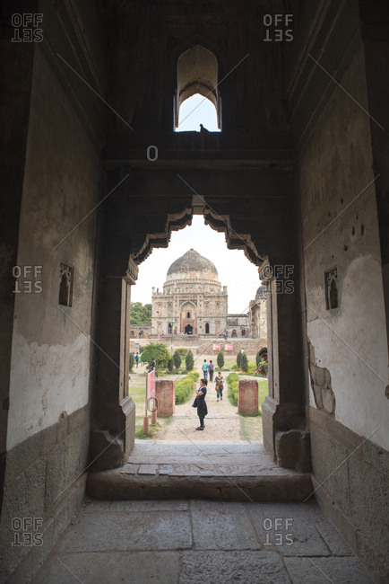 New Delhi, India - March 8, 2017: View through archway to tourists visiting Lodi Gardens, Delhi, India