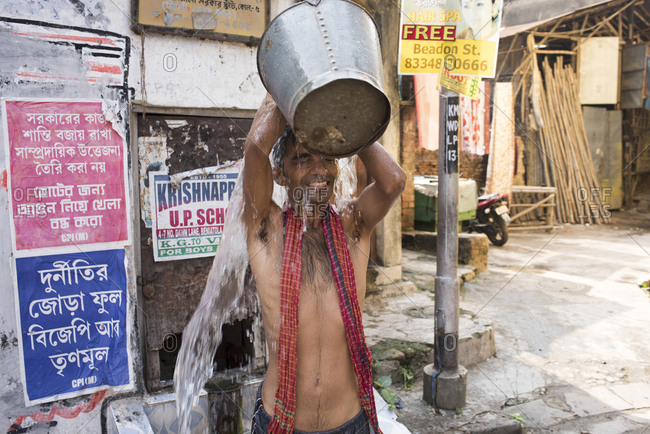 Kolkata, India - March 12, 2017: Young man pouring water over his head during an outdoor bath on the streets of Kolkata, India