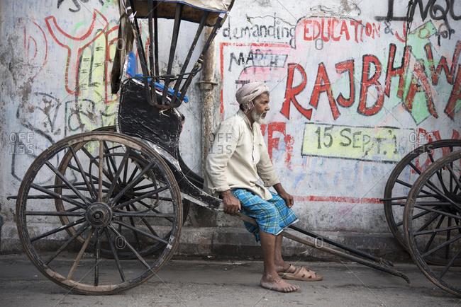Kolkata, India - March 12, 2017: Man resting on his human rickshaw in Kolkata, India