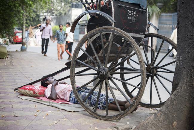 Kolkata, India - March 12, 2017: Man resting under his human rickshaw in Kolkata, India