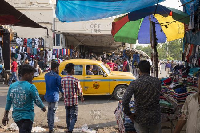 Kolkata, India - March 14, 2017: Street scene with crowds and Ambassador taxi in Kolkata, India