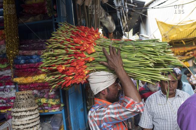 Kolkata, India - March 13, 2017: Man carrying flowers in a market in Kolkata, India