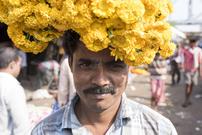 Kolkata, India - March 13, 2017: Man wearing marigolds on his head at a flower market in Kolkata, India