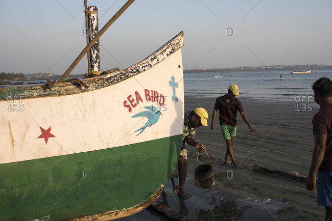 Goa, India - March 14, 2017: Fishermen moving fishing boats on Coco Beach in Nerul, Goa, India