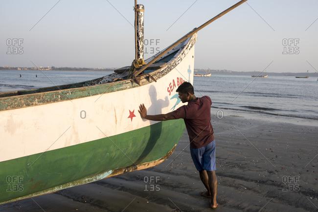 Goa, India - March 14, 2017: Fisherman moving fishing boat on Coco Beach in Nerul, Goa, India