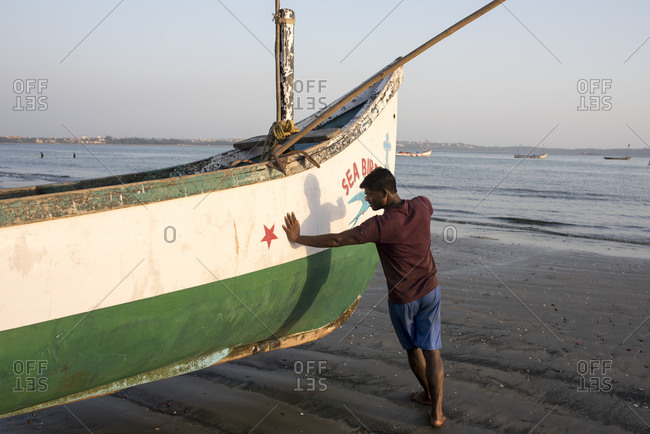 Goa, India - March 14, 2017: Fisherman moving fishing boat on Coco Beach in Nerul, Goa, India