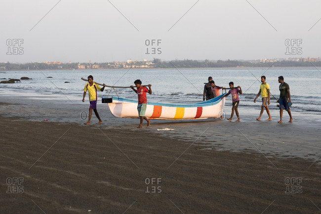 Goa, India - March 14, 2017: Fishermen carrying fishing boats onto Coco Beach in Nerul, Goa, India
