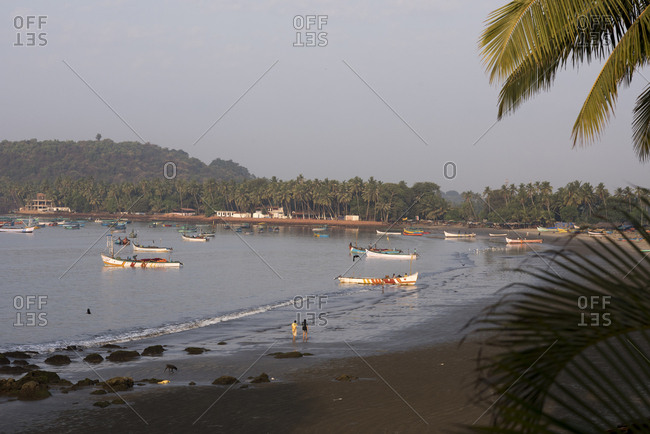Goa, India - March 15, 2017: Fishermen and colorful boats in the water at Coco Beach in Nerul, Goa, India