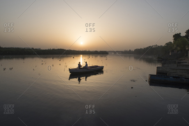Two men feeding birds from a boat on the Yamuna River at sunrise in Delhi, India