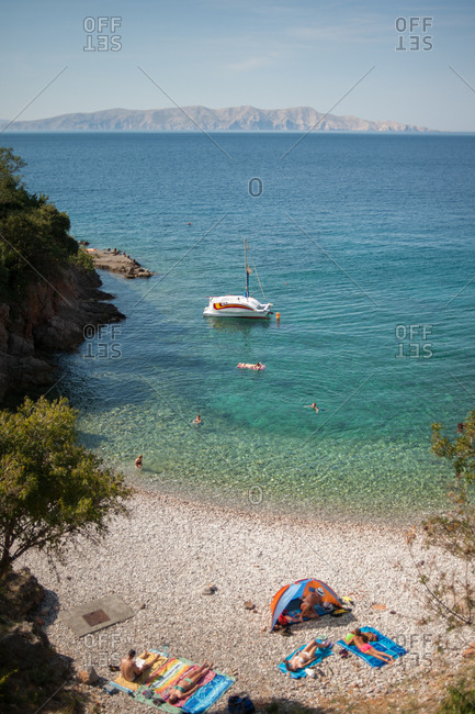 Beachgoers relaxing on a beach in Krk Island, Croatia