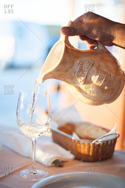 Zadar, Croatia - July 22, 2015: Hand pouring beverage into wine glass