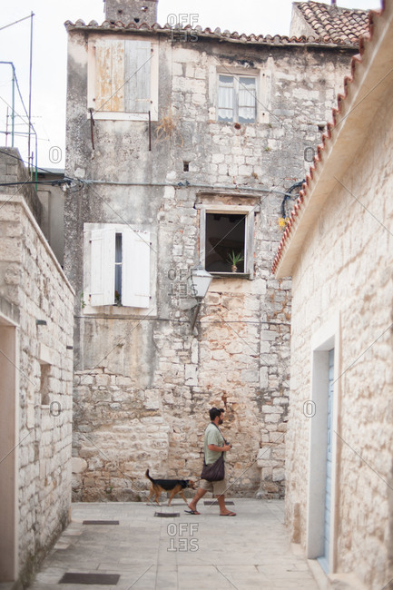 Trogir, Croatia - July 22, 2015: Man walking dog in Trogir, Croatia