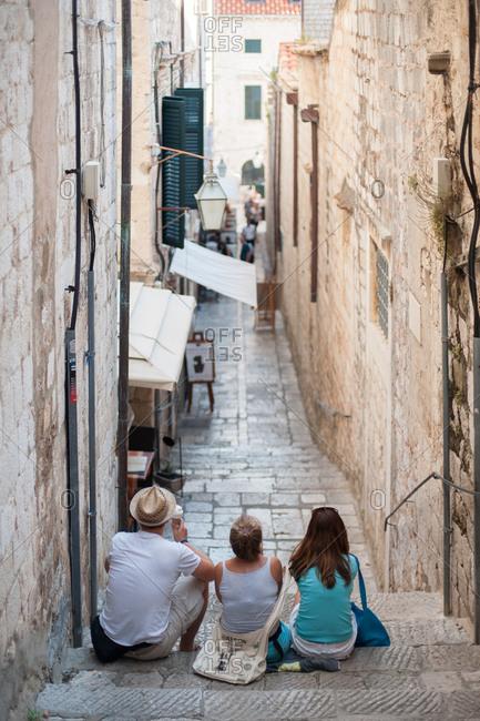 Dubrovnik, Croatia - July 22, 2015: People sitting on steps from behind in Dubrovnik, Croatia