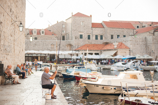 Dubrovnik, Croatia - July 22, 2015: Fisherman fishing in the harbor in Dubrovnik, Croatia