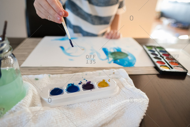 Child holding a paintbrush above a watercolor palette