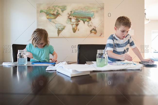 Two children using watercolors to paint pictures together at the table