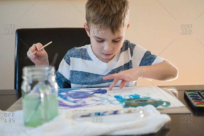 Boy holding a paintbrush while using his finger to blur watercolor paint on paper