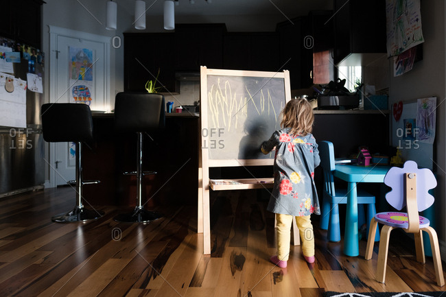 Girl drawing on a chalkboard easel at home