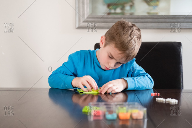 Boy sitting at table using creative toy to make design