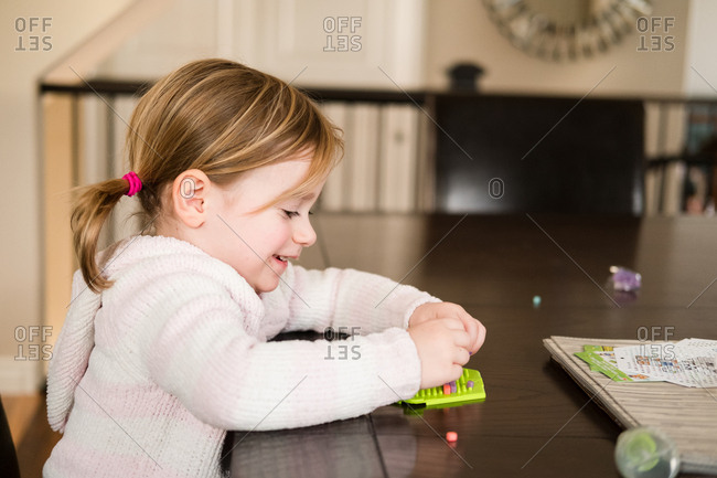 Girl sitting at table using creative toy to make design