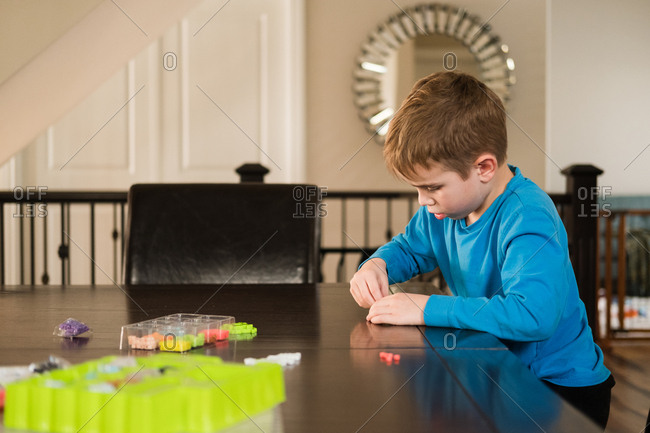 Boy at table working with creative toy
