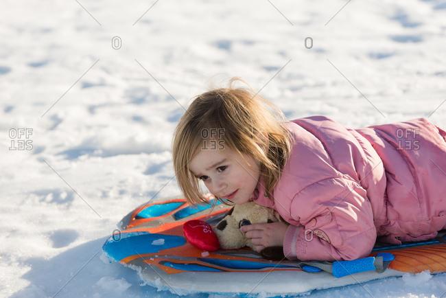 Girl lying on sled with her stuffed animal underneath