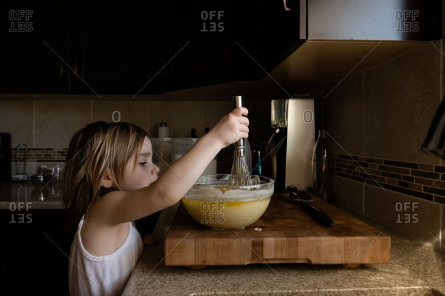 Girl using whisk to stir batter in bowl on cutting board on kitchen counter