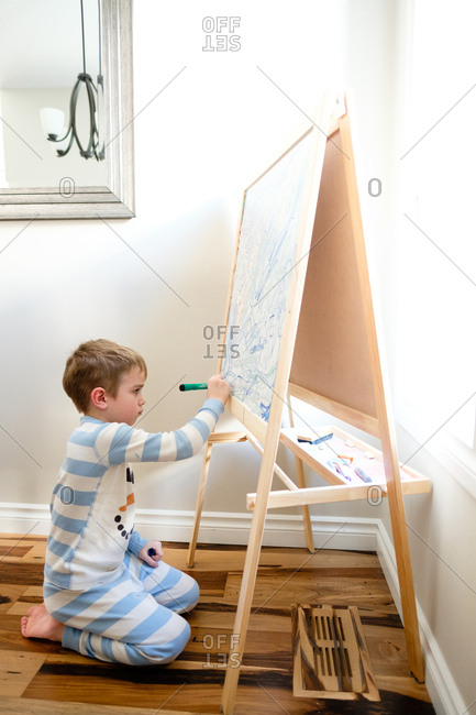 Boy drawing on a whiteboard easel at home