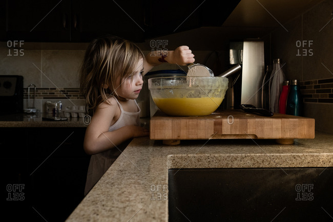 Girl adding flour from measuring cup to batter in bowl on cutting board on kitchen counter