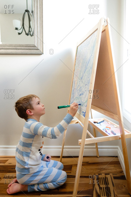 Boy using a marker to add to an elaborate design on a whiteboard easel at home