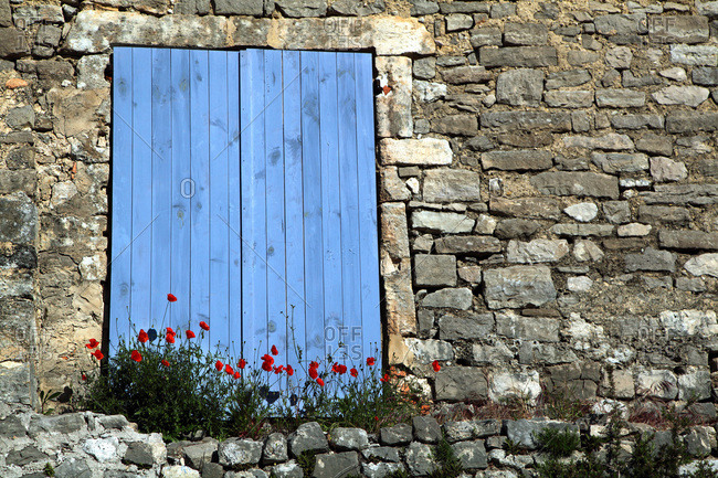 France, Closed blue shutters of a stone house, poppies