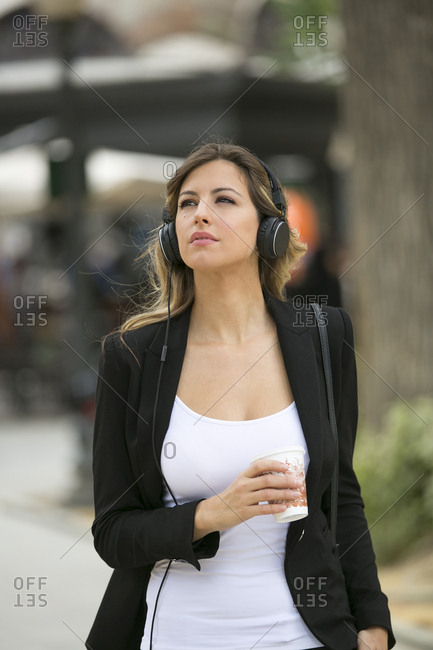 Pretty executive woman with headphones walking in downtown