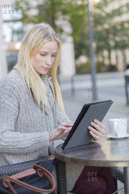 Pretty young woman with tablet in a Cafe in city center