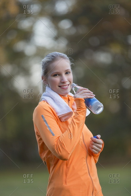 Pretty blonde woman drinking water in park after doing sport and smiling at camera