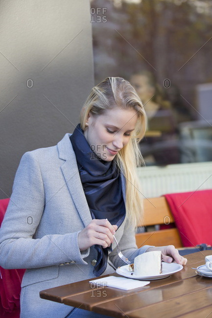 Pretty blonde woman enjoying a cake and coffee in city center